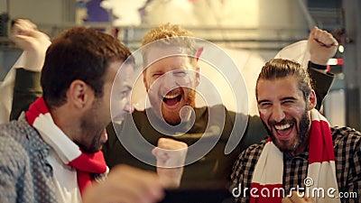 Utmärkta supportrar som tittar på fotbollsmatcher på telefon lager videofilmer