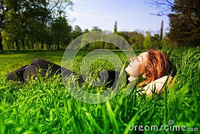 Utomhus- avslappnande kvinna för carefree begreppsgräs