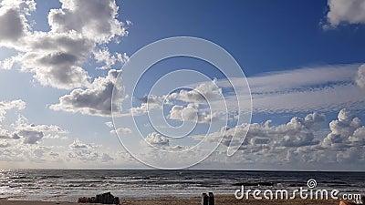 4.000 uur noordzee en zandstrand met blauwe lucht en witte wolken die zich ontwikkelen en veranderen, dynamisch weer stock videobeelden