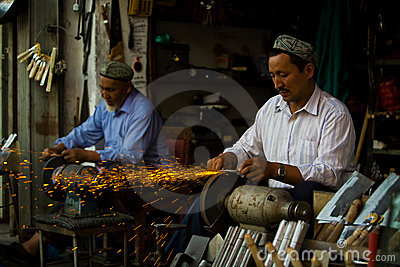 Uyghur craftsmen sharpening knives Editorial Photo