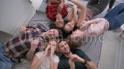 Vänner killar sig, medan ligga på deras baksidor och skratta glatt på kameran under det hem- partiet arkivfilmer