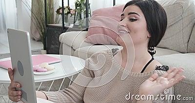Vídeo da mulher que conversa usando a tabuleta digital no apartamento video estoque
