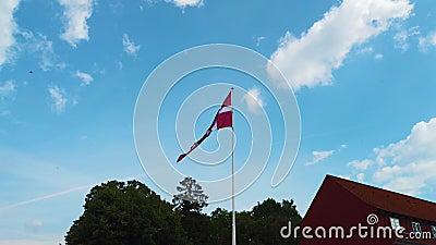 vídeo 4K del danés de la bandera de Dinamarca que sopla en el cielo azul Se sitúa en el centro de Copenhague metrajes