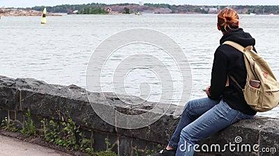 vídeo 4K Una mujer se está sentando en la costa en Helsinki metrajes