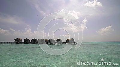 Vacaciones tropicales, cabaña de la casa de planta baja del agua en agua del océano en centro turístico exótico metrajes
