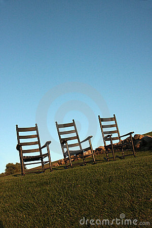 Vacant wooden chairs on grass