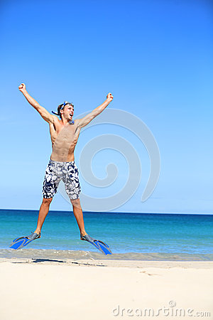 Vacation - happy beach man jumping with snorkeling
