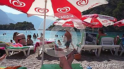 Vacinas e famílias as crianças nadam em lagoa Guarda-sol guarda-chuvas dos solários Editorial video estoque