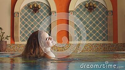 Vackra kvinnor i spa-poolen inomhus Varm, vila, avslappning arkivfilmer