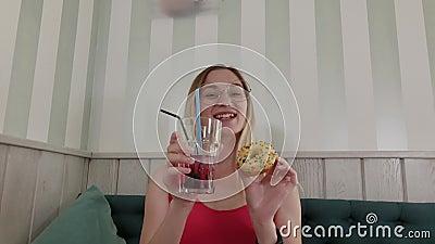 Vackra unga flickor som dansar med en drink och en åsna i händerna när de sitter vid ett bord i en restaurang stock video