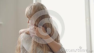 Vackra, vargsamma mor med långt häftigt hår och liten dotter kramar hemma Begreppet moderskap, barndom stock video