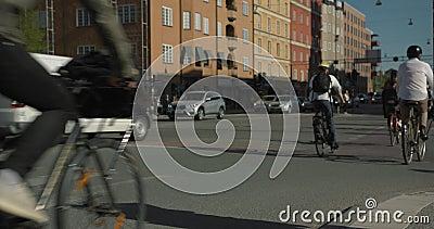 Vada in bicicletta i pendolari che attraversano un'intersezione a Stoccolma centrale Gente anonima sparata al rallentatore, 4K video d archivio
