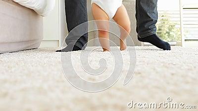 Vader die baby helpen om over deken te lopen stock video