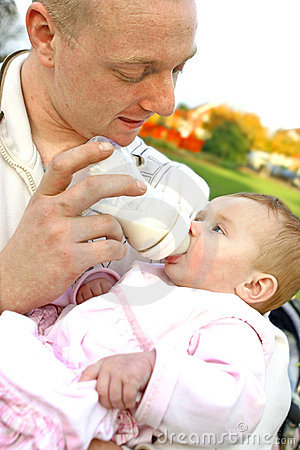 Vader die zijn babymeisje met een fles melk voedt