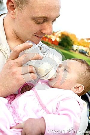 Vader die zijn jonge baby voedt