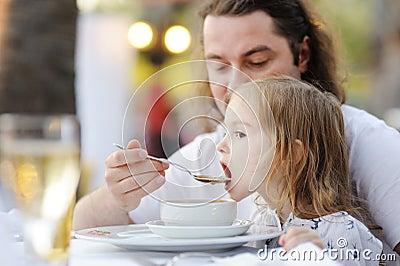 Vader die zijn meisje voedt