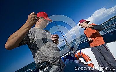 Vader en zoon die op zee vissen