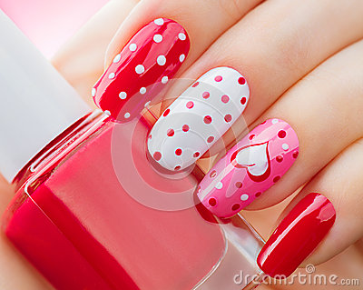 Valentines Day holiday manicure with painted hearts and polka dots Stock Photo