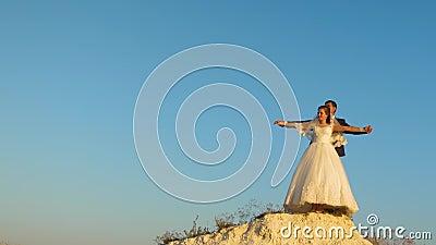 Van de minnaarsbruid en bruidegom holdingshanden tegen blauwe hemel en het glimlachen honeymoon Het concept gezinsleven romantisc stock video
