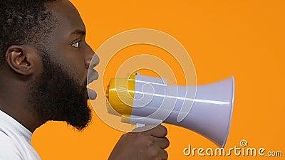 Varón africano joven que grita en el megáfono, acción de la protesta, libertad del discurso, líder metrajes