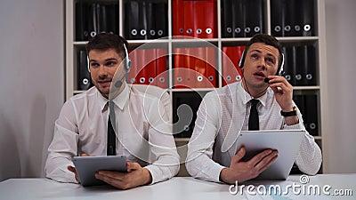 Varón dos en llamada-centro que habla con los clientes por las auriculares metrajes