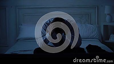 Varón hermoso ansioso en el traje de negocios que se sienta en la cama, manos de frotamiento, problemas metrajes