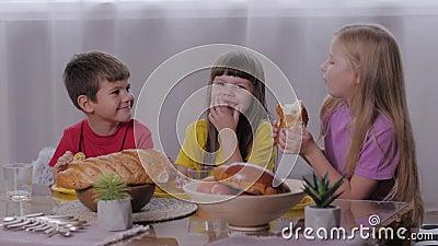 Var försiktig med barndom, lycklig pojke och leende flickor som sitter på sötmat och äter aromatiska pastor efter festen med unga stock video