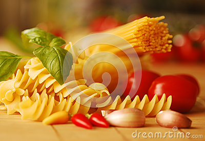 Various types of pasta with basil and tomatoes