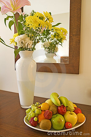 Vase of flowers and fruit on a table