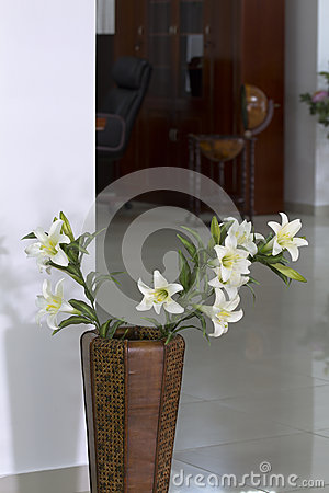 Vase of leather with white lilies.