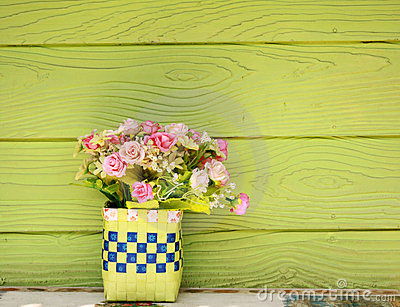 Vase with Plastic flowers and green wall