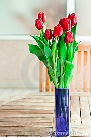 Vase of red flowers on garden table