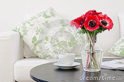 Vase of red flowers in modern white living room