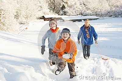 Vater und Kinder, die Schlitten herauf Snowy-Hügel ziehen