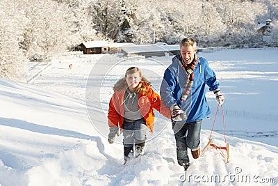 Vater und Sohn, die Schlitten herauf Snowy-Hügel ziehen