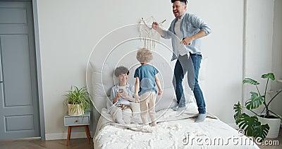 Vater und Sohn springen zuhause im Bett, während Mutter mit Smartphone lächelt stock video