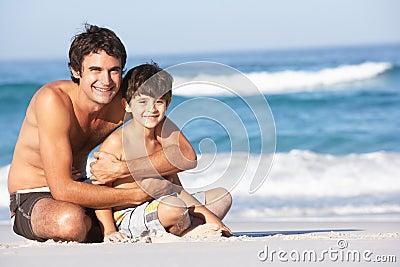 Vater-und Sohn-tragende Badebekleidung, die sich hinsitzt