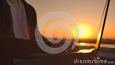 Vault-Plan für Handtippen auf einer Notebook-Tastatur bei Sonnenuntergang mit Blick auf die Stadt von einer Höhe aus Programmiere stock video