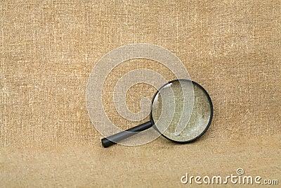 Vecchio magnifier nero sulla priorità bassa del drapery