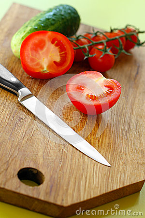 Vegetables and knife on wooden cutting board
