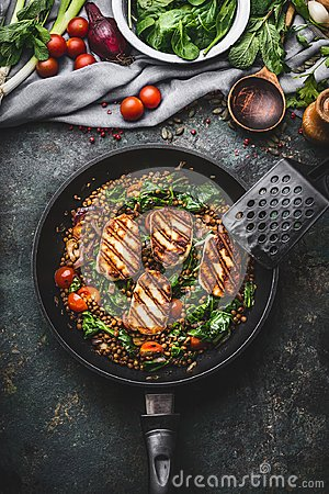 Free Vegetarian Food Concept. Healthy Lentil Meal With Spinach And Fried Cheese In Cooking Pan On Rustic Background With Ingredients Stock Image - 104115501