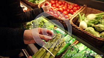 Vegetarisches Mädchen wählt ein Bündel frischen organischen Spargel am lokalen Supermarkt vor stock video footage