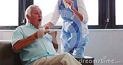 Velas que soplan del hombre mayor hacia fuera con la enfermera almacen de video