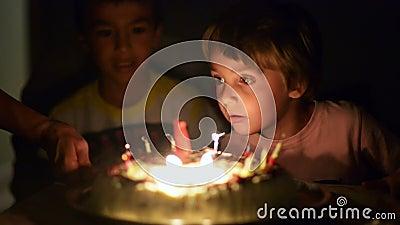 Velas que soplan del niño feliz en su aniversario metrajes