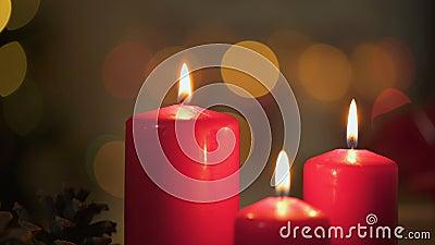 Velas rojas que queman, luces de la Navidad que centellean en el fondo, tiempo milagroso almacen de video