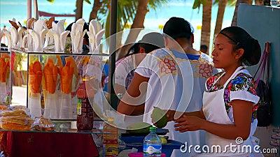 Vendedores ambulantes de la fruta y del coco del mango en el Playa del Carmen, México almacen de video