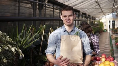 Venditrice allegra in grembiule nero che distribuisce verdure fresche in sacchetto di carta al cliente sul mercato dei gas serra  archivi video