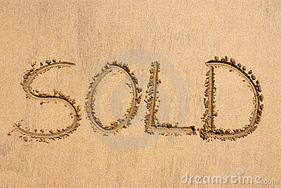 «Vendu» écrit sur le sable
