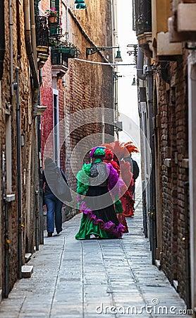 Venetian dräkter på en smal gata i Venedig Redaktionell Arkivbild