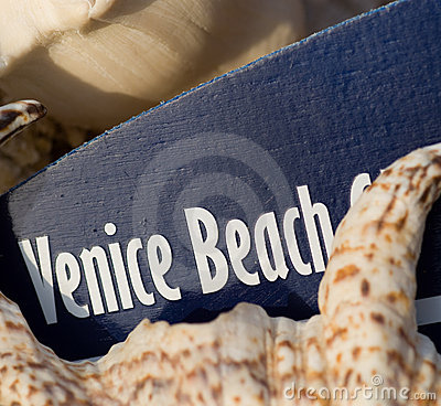Venice Beach surfboard sign on shell beach
